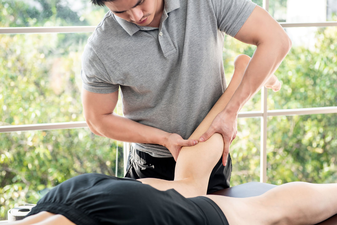 man massaging athlete's leg for benefits of neuromuscular massage and trigger point therapy